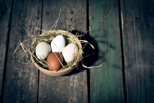 Easter nest with eggs in bowl on dark wood - MAEF010243