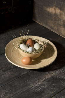 Easter nest with eggs in bowl on dark wood - MAEF010244