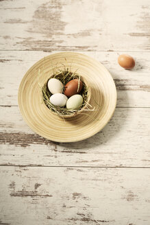 Easter nest with eggs in bowl on wood - MAEF010247