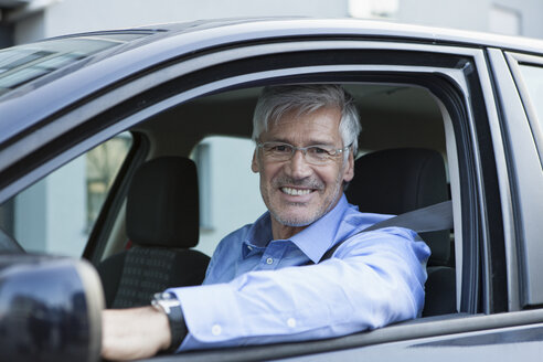 Portrait of smiling businessman sitting in his car - RBF002606