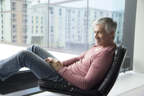 Man relaxing in a leather chair at home - RBF002656