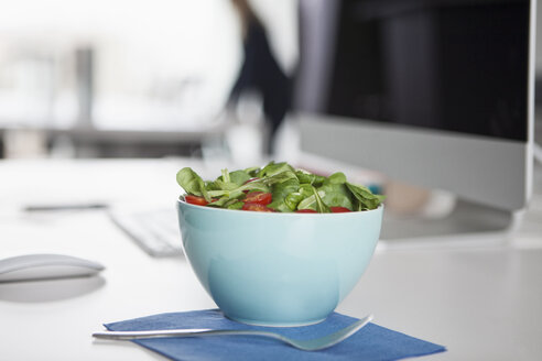 Bowl with garnished salad on a desk in an office - RBF002611