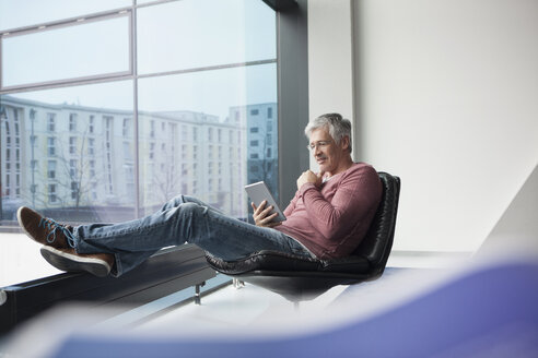 Man sitting in a leather chair using digital tablet - RBF002614