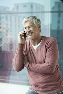 Portrait of smiling man telephoning with smartphone - RBF002635