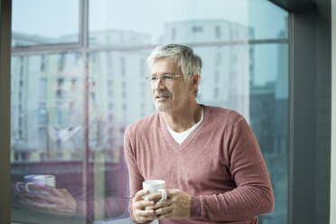 Portrait of man with coffee cup looking through window - RBF002638
