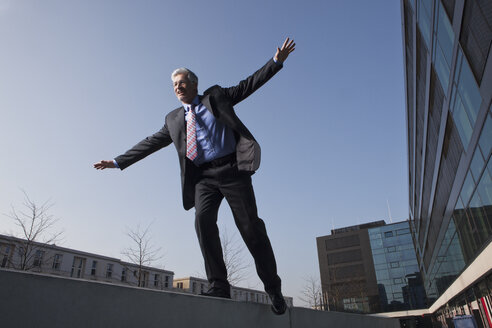Businessman balancing on a wall - RBF002641