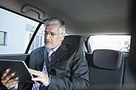 Businessman sitting in a car using digital tablet - RBF002647