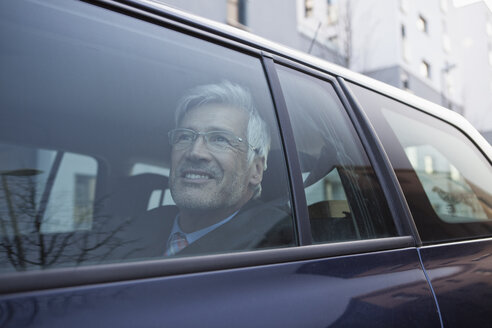 Smiling businessman looking through window of his car - RBF002650