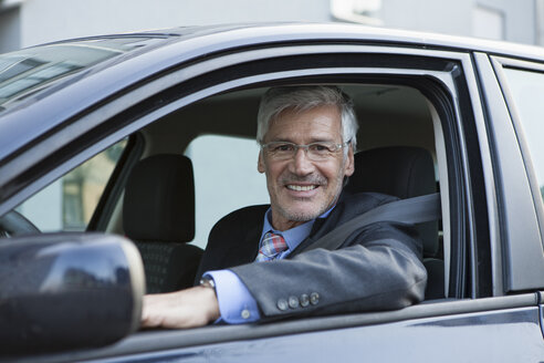 Portait of smiling businessman sitting in his car - RBF002653