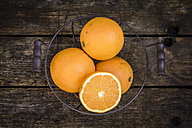 Sliced and whole oranges in a wire basket - SARF001704