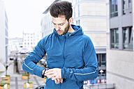 Germany, Magdeburg, young man looking at his heart rate monitor - SEGF000328