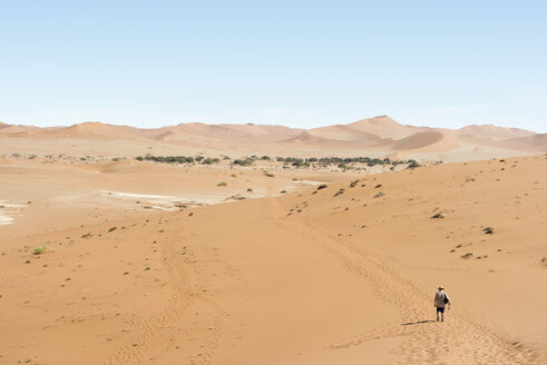 Namibia, Namib Desert, Namib Naukluft Park, Sossusvlei, man walking through the desert - CLPF000101