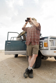Namibia, Etosha National Park, Man leaning on car looking through binoculars - CLPF000120