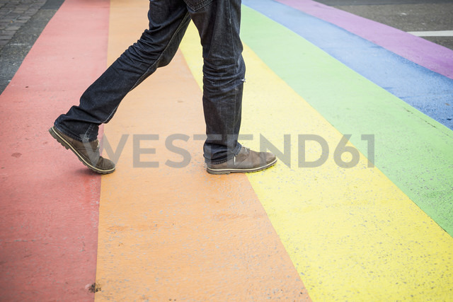 Netherlands, Maastricht, man walking on rainbow flag painted on the street - RIBF000028