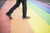 Netherlands, Maastricht, man walking on rainbow flag painted on the street - RIBF000028