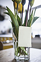 Adhesive note on a glass with tulips on a kitchen table - RIBF000020