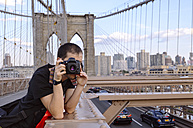 USA, New York, traveller taking pictures of Manhattan from Brooklyn Bridge in the evening - GEMF000204
