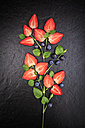 Symbolic flower shaped of sliced strawberries, melissa and blueberries on slate - VTF000419