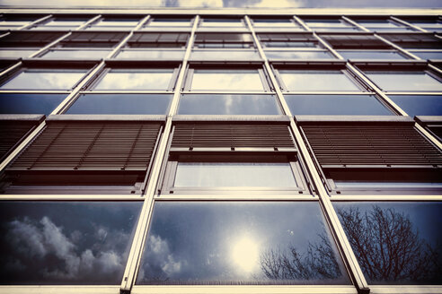 Germany, Bochum, facade of an office building with reflections od cun and clouds - HOHF001342
