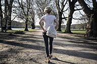 Germany, Cologne, single woman walking at city park - RIBF000030