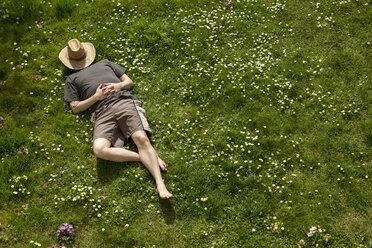 Man lying in grass relaxing - MIDF000320