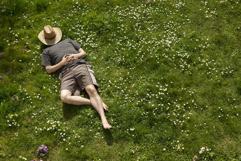 Man lying in grass relaxing - MIDF000320