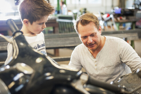 Father and son maintaining vintage moped - PAF001274