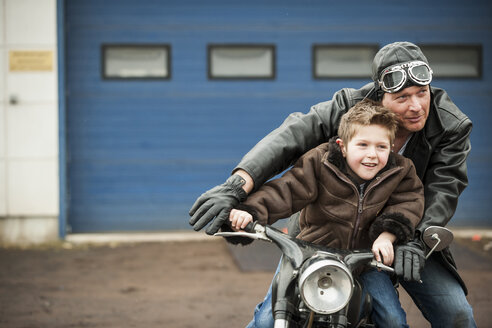 Father and son driving with vintage moped - PAF001284