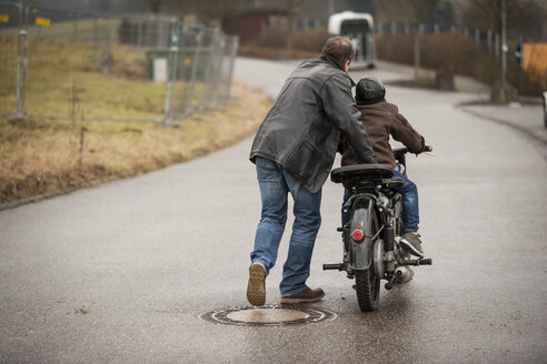 Father and son driving with vintage moped - PAF001295