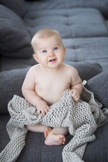 Portrait of naked baby girl sitting on a couch - JTLF000100