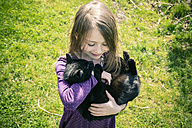 Little girl carrying black cat - SARF001728