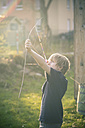 Boy using bow self-built of twigs and looms - SARF001724