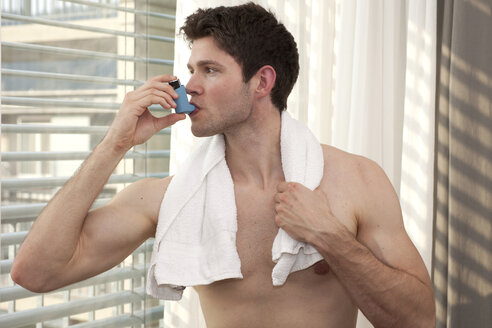 Young man using asthma inhaler - DHLF000527
