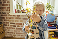 Little boy holding vase with willow catkin and forsythia - MFF001580