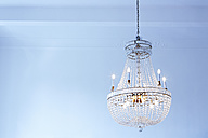 Lighted old ceiling lamp in front of light blue wall - DISF002021