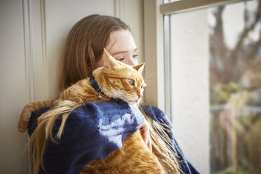 Female teenager with cat looking through window - DISF002028