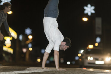 Young man walking on his hands on pavement at night - ZEF005337