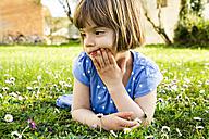 Pensive little girl lying on a meadow - LVF003195