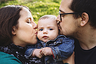 Mother and father kissing baby outdoors - GEMF000213