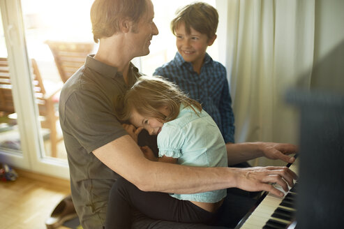 Father playing piano with daughter on his lap, son watching - MAO000053