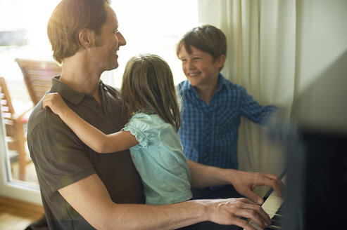 Father playing piano with daughter on his lap, son watching - MAO000037