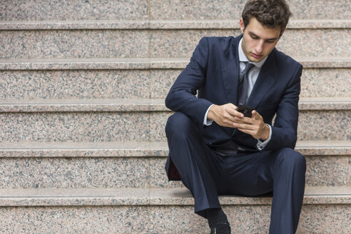Portrait of young businessman sitting on stairs using smartphone - ABZF000004