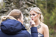 Female visagiste applying lipstick on young woman's lips - DAWF000340