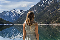 Austria, Tyrol, Lake Plansee, woman at lakeshore - TCF004603