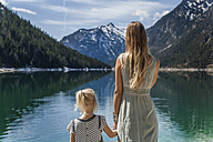 Austria, Tyrol, Lake Plansee, mother and daughter at lakeshore - TCF004622