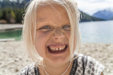 Austria, Tyrol, Lake Plansee, portrait of girl pulling a face - TCF004627
