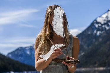 Austria, Tyrol, Lake Plansee, woman building up model sailboat - TCF004628