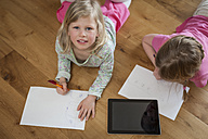 Two sisters with digital tablet and sheets of paper on floor - PAF001320