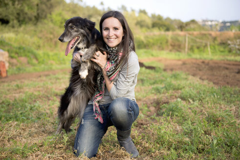 Smiling woman holding dog outdoors - GEMF000221