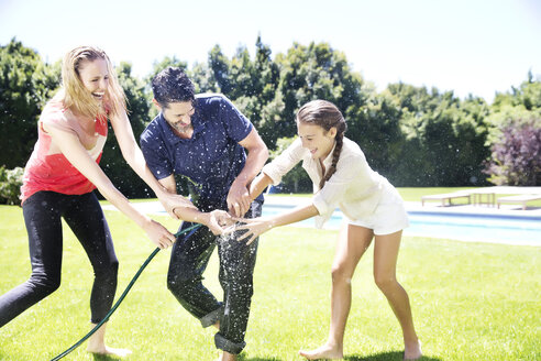 Happy family splashing water with garden hose - TOYF000058